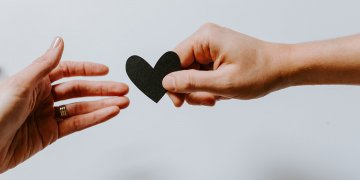 person giving a small black heart