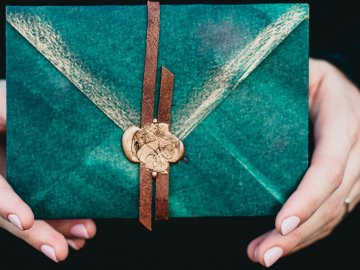 person holding green envelope