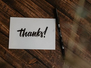 thank you card on table next to black pen